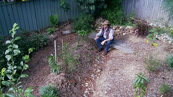 Geoff Lawton sitting in a mini swale backyard system