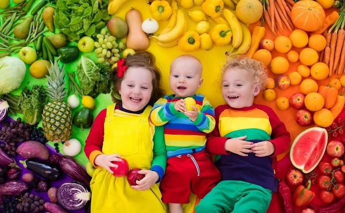 Boy, girl and baby with variety of fruit and vegetable. Colorful rainbow of raw fruits and vegetables. Child eating healthy snack. Vegetarian nutrition for kids. Vitamins for children. View from above