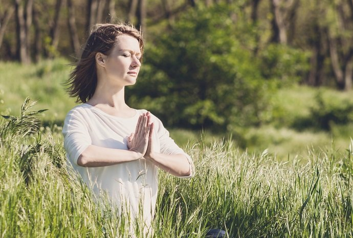 A young woman meditating in park at the sunrise