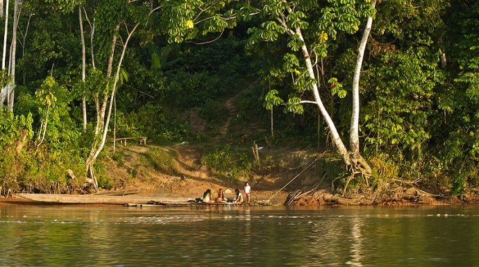 Unidentified local indigenous people next to Napo river in the rainforest, Yasuni National Park, Ecuador