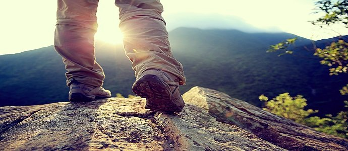 woman hiker legs stand on mountain peak rock